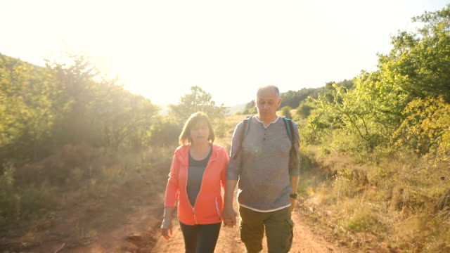 front view of senior couple trekking on sunny autumn day - baby boomer stock videos & royalty-free footage