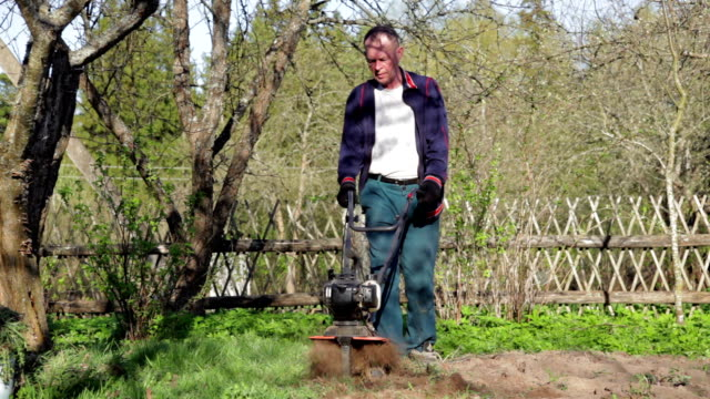 Front view of the man cultivating the ground with the garden cultivator