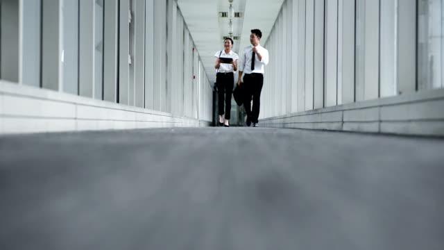 vidéos et rushes de vue avant de deux jeunes collègues parlant et marchant au corridor - moquette
