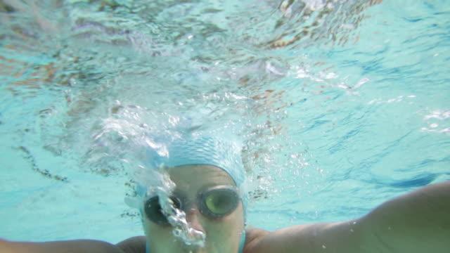 vídeos de stock e filmes b-roll de cu ts front view of woman swimming breast stroke shot from underwater. - touca de natação