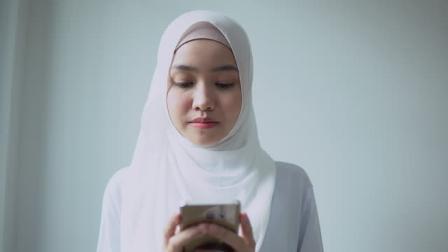 front view of young asian woman in hijab using mobile phone at home - malaysia stock videos & royalty-free footage