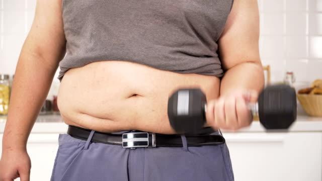 正面: 太りすぎの男彼の健康とキッチンの形になって運動 - きつい点の映像素材/bロール