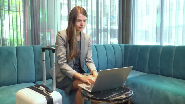 front view: russian beautiful businesswoman wearing formal clothes and wheeled luggage working business on a laptop while waiting for a colleague in the lobby of a luxury hotel resort. concept of business travel in the hotel - guest stock videos & royalty-free footage