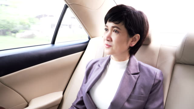 front view: senior business woman looking the view while being in the car - solo una donna matura video stock e b–roll