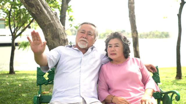 vidéos et rushes de vue de face: couple de personnes âgées passe du temps ensemble dans le parc - picnic