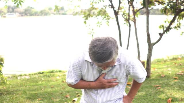 vídeos de stock, filmes e b-roll de vista frontal: homem sênior ainda é jovem, mas ele se sinta mal em seu coração e ele chamar alguém para ajudar! - heart attack