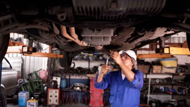 正面: レンチ下の古い車メカニック年配の男性固定 - 作業道具点の映像素材/bロール