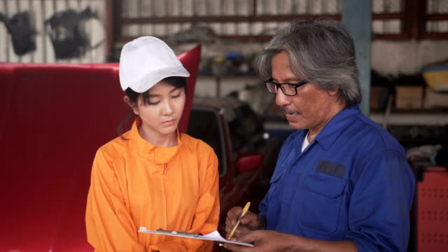 Front view: The senior mechanic teach Asian young female car mechanic for Working