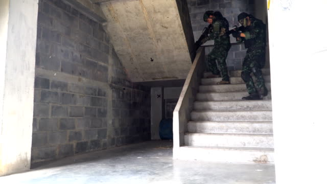 front view: two fully Equipped and Armed Soldiers walking down on ladder to patrol in unknown house