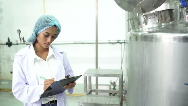front view: young  female industrial scientist check the storage tanks. she work at the beverage production line - manufacturing occupation stock videos & royalty-free footage