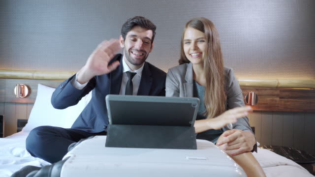 front view:asian businessman and russian beautiful businesswoman wearing formal clothes sitting on white bed having business meeting, discussing on digital tablet laying on  wheeled luggage with positive emotion of smiling in the luxury hotel resort room. - 25 29 years stock videos & royalty-free footage