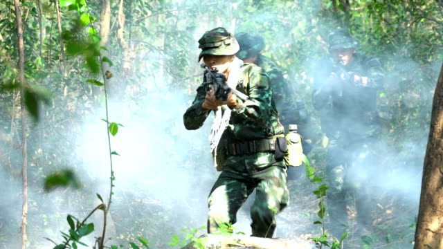 front view:group of fully Equipped and Armed Soldier is patrolling in tropical forest