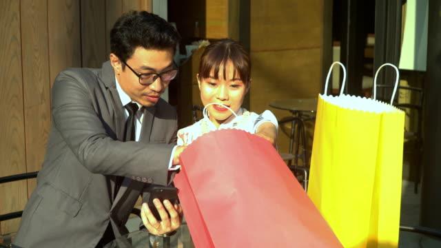 stockvideo's en b-roll-footage met voorste weergave: jonge zakenman en chinese vriendin in het chinees jurk vinden van iets in het winkelen van de papieren zak - cadeau