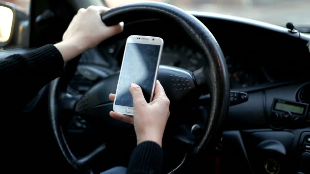 Frontal view of modern smart phone with blank white screen with copy space for your text or design, close up of driver hands using mobile phone in car
