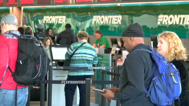 frontier airlines ticket counter busy at denver international airport. passengers at the ticket counter on a typical morning in the terminal at dia. - dia stock videos & royalty-free footage