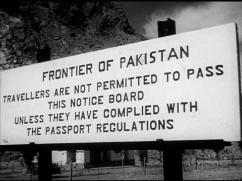 'frontier of pakistantravellerspasspassport regulations' border sign xws fort vs caravan w/ limping camel people walking down some w/ donkeys under... - pakistan stock videos and b-roll footage