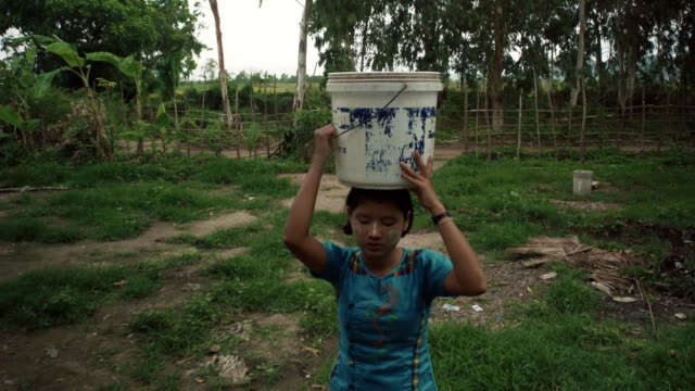 w/s-m/s steadycam frontshot, burmese teenage girl carrying water to her house in a rural area - carrying stock-videos und b-roll-filmmaterial