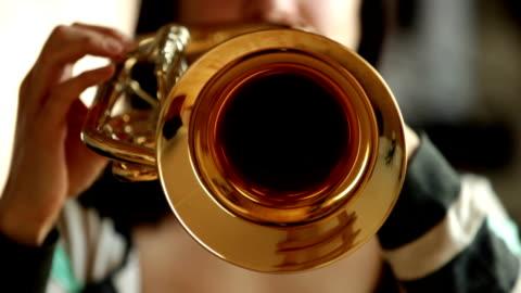 front-view of woman playing flugelhorn / trumpet - musikinstrument bildbanksvideor och videomaterial från bakom kulisserna