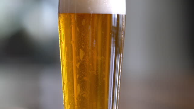 a frosty mug glass of beer with foam head - lager stock videos & royalty-free footage