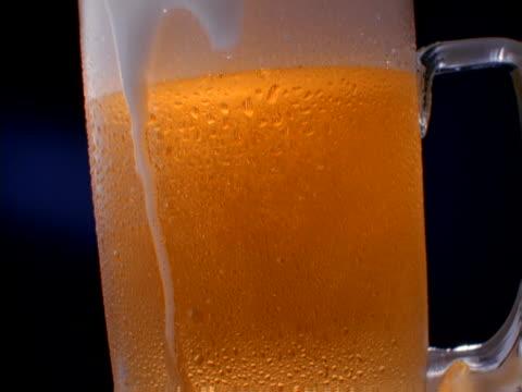 vídeos y material grabado en eventos de stock de a frosty mug of foamy beer - frío