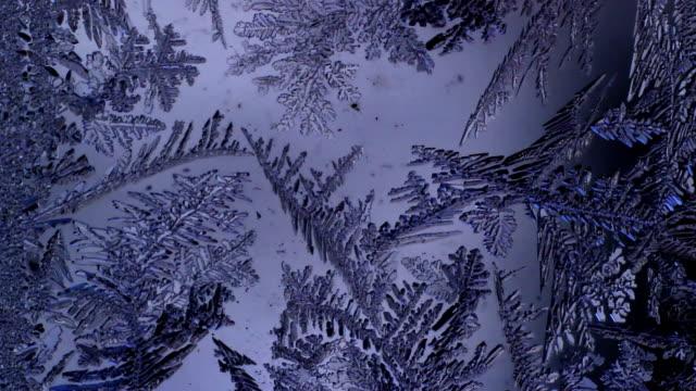Frosty pattern melts on the glass