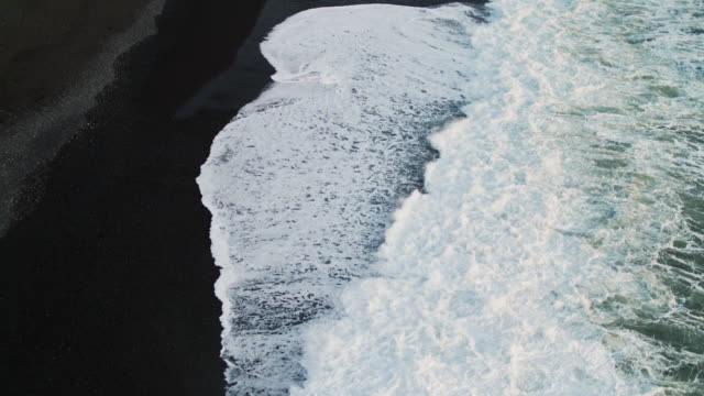 frothy white waves hitting black sand beach - aerial - black sand stock videos & royalty-free footage