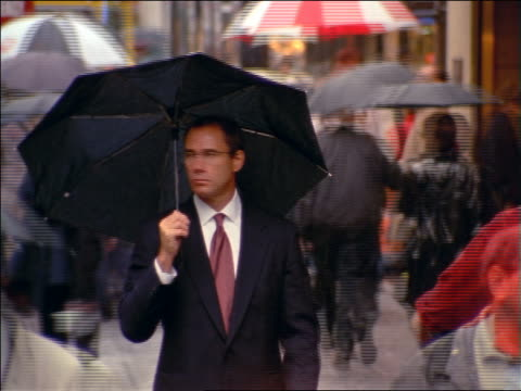 Frowning businessman with umbrella standing looking around on sidewalk as time lapse people walk past him