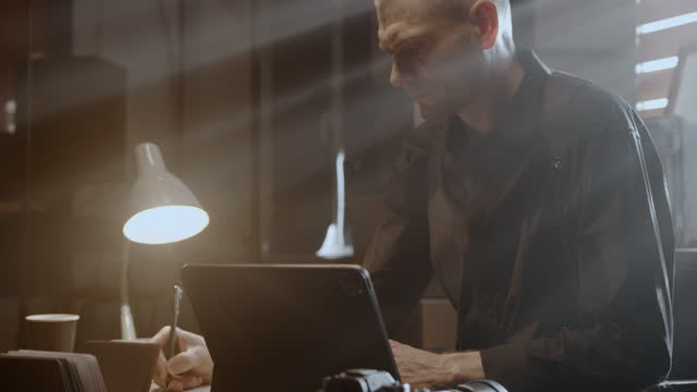 a frowning focused man is sitting at a table and working with documents - detective stock videos & royalty-free footage