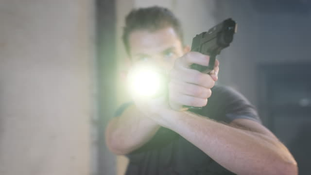 frowning police officer holding flashlight and aiming pistol - detective stock videos & royalty-free footage