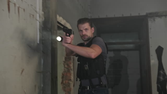 frowning polizist hält taschenlampe und zielpistole - schusswaffe stock-videos und b-roll-filmmaterial