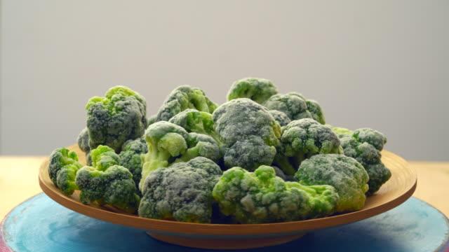 brokkoli gefroren. grüner brokkoli-hintergrund mit eis und frost. gefrorenes gemüse - eingefroren stock-videos und b-roll-filmmaterial