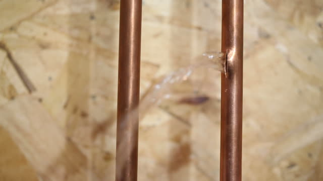stockvideo's en b-roll-footage met frozen cracked copper water pipe leaking into house basement - beschadigd