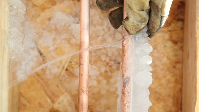 stockvideo's en b-roll-footage met frozen cracked copper water pipe leaking into house basement - bevroren