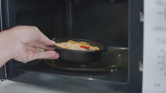 電子レンジで冷凍食品の加熱、ビデオモンタージュ - 電子レンジ点の映像素材/bロール