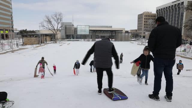 vídeos de stock e filmes b-roll de frozen highways, snow shoveling and people sledding after snow storm in midland, texas, u.s., on monday, february 15, 2021. - pá para neve