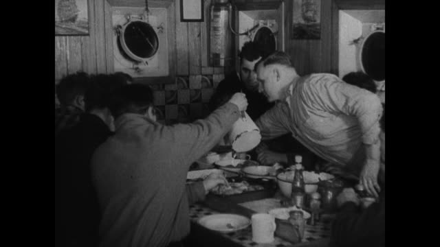 vídeos de stock, filmes e b-roll de frozen ice covered deck rails of steam trawler int boat w/ fisherman checking depth gauge standing next to compass dramatization crew eating at table... - compasso