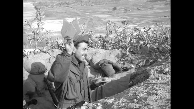 vs frozen imjin river and mountains around it during korean war / soldier in foxhole looks through stack of envelopes holds them up and smiles /... - trench stock videos & royalty-free footage