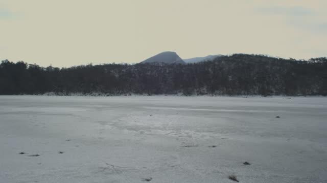 Frozen lake and volcano in background, Kirishima, Japan, February 2011