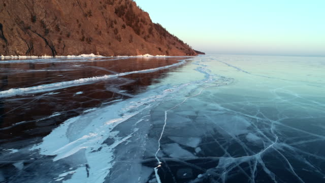 frozen lake baikal by mountain against sky sunset - frozen water stock videos & royalty-free footage
