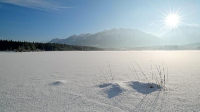 vídeos de stock, filmes e b-roll de frozen lake barmsee with karwendel mountainrange on morning with sun in winter, krün, garmisch-partenkirchen upper bavaria, bavaria, germany, european alps - alta baviera