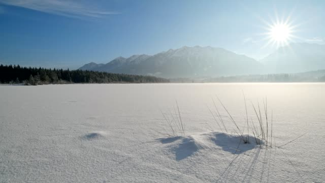 vídeos de stock, filmes e b-roll de frozen lake barmsee with karwendel mountainrange on morning with sun in winter, krün, garmisch-partenkirchen upper bavaria, bavaria, germany, european alps - garmisch partenkirchen