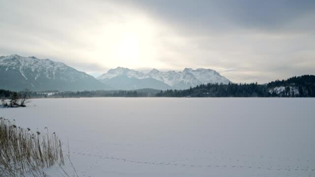 frozen lake barmsee with karwendel mountainrange on morning with sun in winter, krün, garmisch-partenkirchen upper bavaria, bavaria, germany, european alps - garmisch partenkirchen stock videos & royalty-free footage