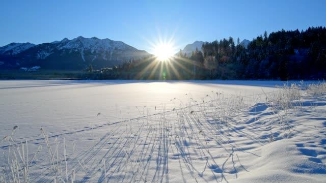 frozen lake barmsee with karwendel mountainrange on morning with sun in winter, krün, garmisch-partenkirchen upper bavaria, bavaria, germany, european alps - frozen stock videos and b-roll footage