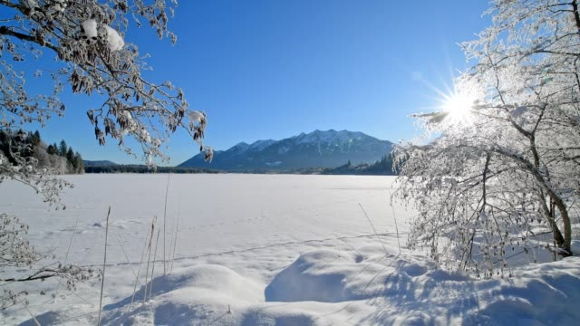 frozen lake barmsee with karwendel mountainrange on morning with sun in winter, krün, garmisch-partenkirchen upper bavaria, bavaria, germany, european alps - krün stock videos and b-roll footage