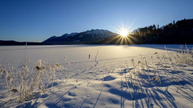 frozen lake barmsee with karwendel mountainrange on morning with sun in winter, krün, garmisch-partenkirchen upper bavaria, bavaria, germany, european alps - garmisch partenkirchen stock videos and b-roll footage