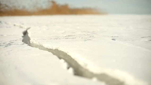 frozen lake surface cracking on sunny day - lake stock videos & royalty-free footage