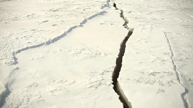 vidéos et rushes de surface gelée du lac fissuration par journée ensoleillée - ouverture du diaphragme