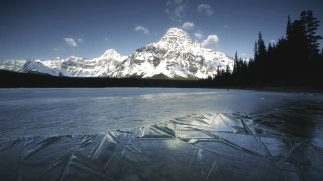 vídeos de stock, filmes e b-roll de t/l ws frozen lake surrounded with snowcapped mountains, banff national park, alberta, canada - terreno extremo