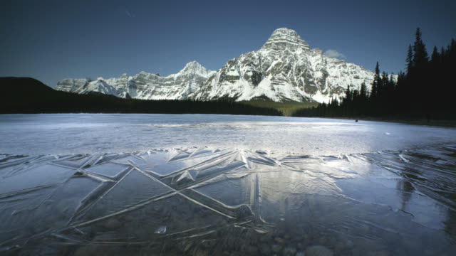 t/l ws frozen lake surrounded with snowcapped mountains, banff national park, alberta, canada - eingefroren stock-videos und b-roll-filmmaterial