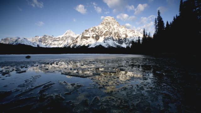 t/l ws frozen lake surrounded with snowcapped mountains, banff national park, alberta, canada - montagne rocciose video stock e b–roll